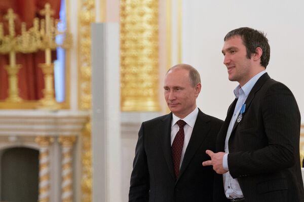 Президент России Владимир Путин (слева) и нападающий сборной по хоккею Александр Овечкин на церемонии награждения национальной сборной