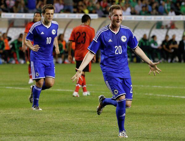 Футболисты сборной Боснии и Герцеговины Звездан Мисимович и Изет Хайрович радуются забитому мячу в ворота мексиканцев