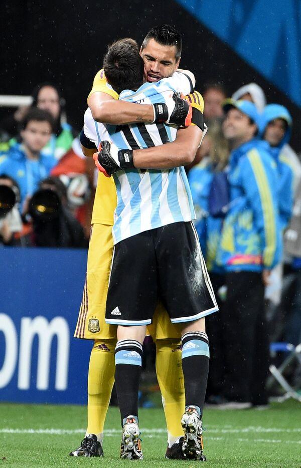 Серхио Ромеро и форвард сборной Аргентины Лионель Месси (справа) радуются победе.