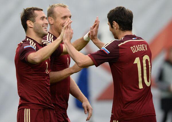 Футболисты сборной России Алан Дзагоев, Денисо Глушаков поздравляют Александра Кержакова с забитым мячом
