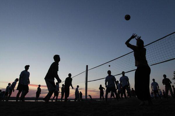 Молодые спортсмены играют на закате в волейбол