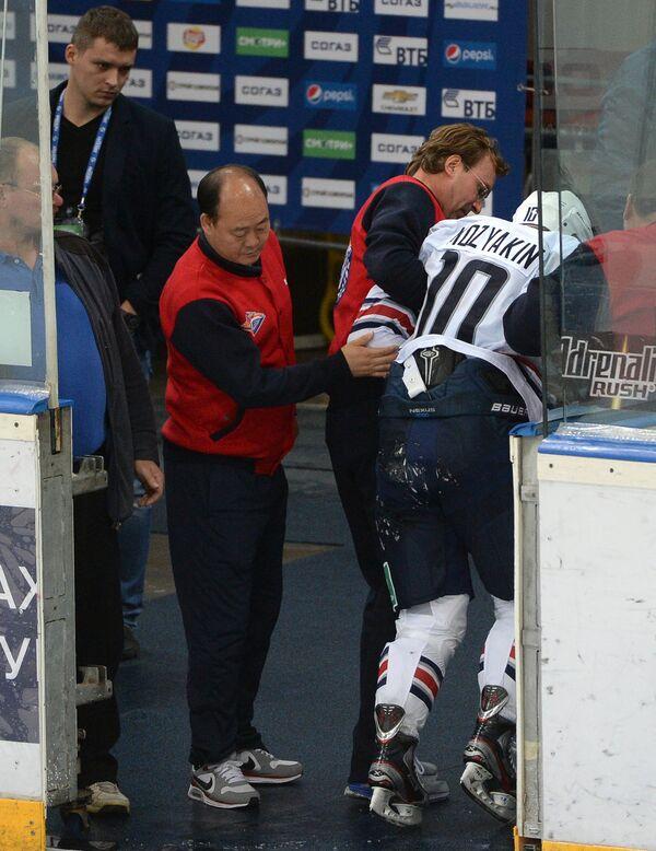 Медики уводят получившего травму форварда ХК Металлург Сергея Мозякина (справа)