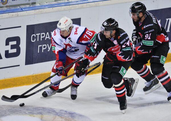 Нападающий Локомотива Алексей Кручинин и хоккеисты Авангарда Александр Попов и Никита Пивцакин (слева направо)