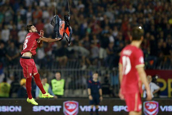 Защитник сборной Сербии Стефан Митрович ловит албанский флаг