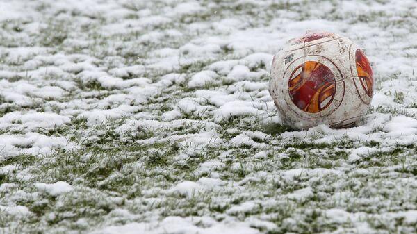 Футбольный мяч на заснеженном поле