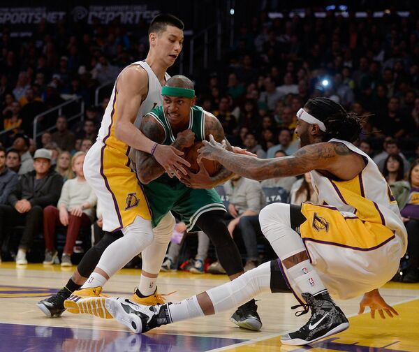 Разыгрывающий Бостона Исайа Томас в борьбе за мяч с баскетболистами Лейкерс Джереми Лином и Джорданом Хиллом