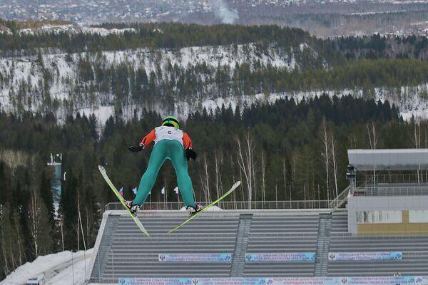 Спортсмен в соревнованиях летающих лыжников на зимней Спартакиаде