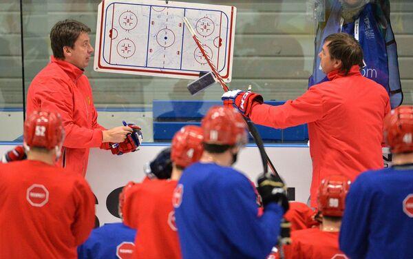 Тренер сборной России по хоккею Харийс Витолиньш (слева) и главный тренер сборной Олег Знарок (справа) во время тренировки