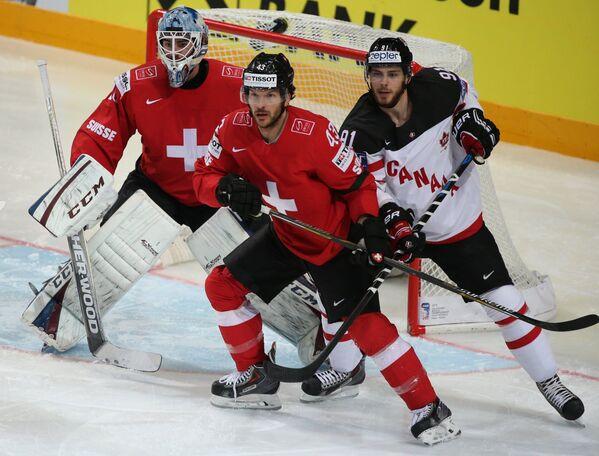Вратарь Швейцарии Леонардо Дженони, нападающие сборной Швейцарии Моррис Трахслер и сборной Канады Тайлер Сегин (слева направо)