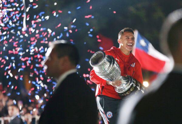 Нападающий сборной Чили Алексис Санчес с трофеем за победу на Кубке Америки