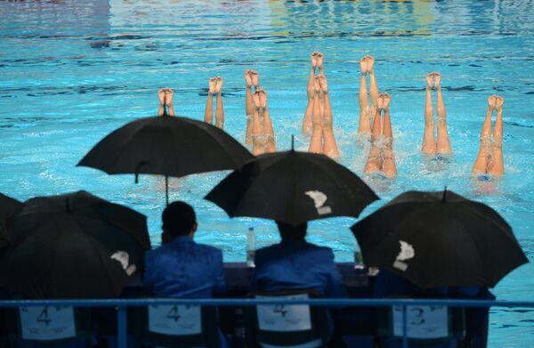 Судейская бригада наблюдает за выступлением в произвольной программе в комбинации команды сборной КНДР на соревнованиях по синхронному плаванию
