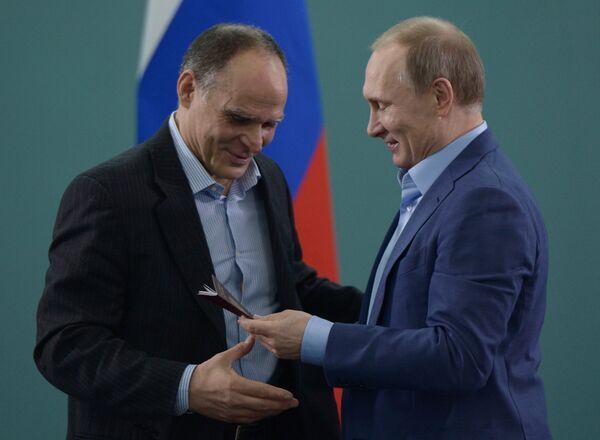 Президент России Владимир Путин (справа) вручает паспорт гражданина РФ тренеру сборной команды России по дзюдо Эцио Гамбе
