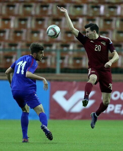 Нападающий сборной Молдавии Евгений Ребенжа (слева) и полузащитник сборной России Евгений Кирисов