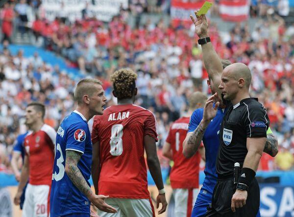 Главный судья Шимон Марциняк (справа) выносит предупреждение защитнику сборной Исландии Ари Скуласону (слева)